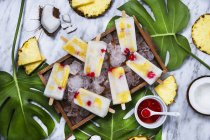 Pina Colada popsicles with candied cherries and pineapple on leaves - foto de stock