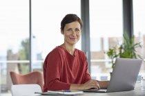 Портрет улыбающейся женщины, сидящей за столом дома с помощью ноутбука — стоковое фото