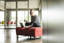 Молодий підприємець працює в сучасному офісі, сидячи на стільці, використовуючи ноутбук — стокове фото