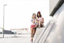 Лучшие друзья со скейтбордом, веселятся вместе, слушают музыку — стоковое фото