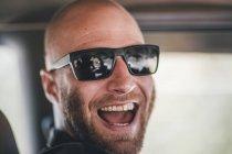 Портрет счастливого молодого человека в солнечных очках и с бородой в поездке — стоковое фото