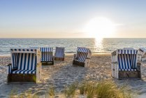 Germany, Schleswig-Holstein, Sylt, beach and empty hooded beach chairs at sunset — Stock Photo