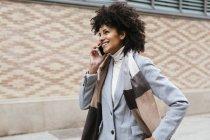 Mulher sorrindo no celular andando na cidade — Fotografia de Stock