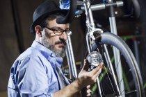 Homme travaillant sur vélo en atelier — Photo de stock