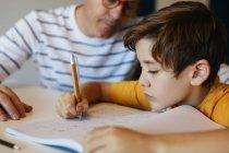 Отец смотрит, как сын делает домашнее задание дома — стоковое фото