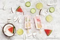Homemade watermelon coconut ice lollies with lime and cucumber slices, fresh coconut and watermelon pieces on ice cubes — Foto stock