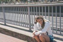Sorridente sportiva giovane donna seduta in autostrada — Foto stock