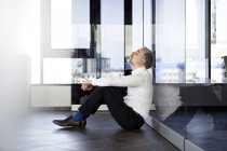 Businessman sitting on the floor in office with closed eyes — Stock Photo