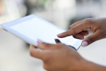 Close-up of woman's hands using tablet outdoors — Stock Photo