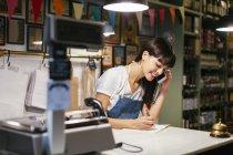 Усміхнена жінка по телефону в магазині, беручи нотатки — стокове фото