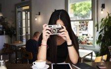 Morena menina tirando uma foto com sua câmera de filme em um café — Fotografia de Stock