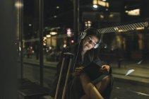 Ritratto di giovane donna con cuffie e tablet in attesa alla stazione di notte — Foto stock