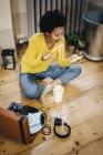 Молодая африканская американка сидит рядом с проигрывателем, проверяет смартфон и ест лапшу дома — стоковое фото