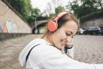 Смолящая спортивная молодая женщина в наушниках на улице — стоковое фото