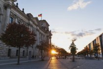 Allemagne, Berlin, Regierungsviertel, bâtiment de Reichstag avec des drapeaux allemands et Paul-Loebe-Bâtiment au coucher du soleil — Photo de stock