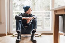 Cool senior man sitting on ground, looking out of window — Stock Photo