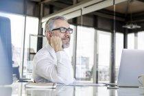 Homme d'affaires souriant avec ordinateur portable au bureau dans la pensée de bureau — Photo de stock