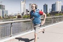 Зрелый мужчина в наушниках, бегающий по мосту в городе — стоковое фото