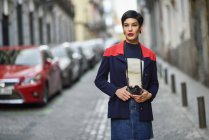 Portrait of fashionable young woman with camera on the street — Stock Photo