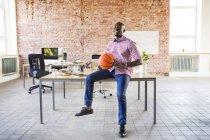 Felice uomo d'affari con pallacanestro alla scrivania in ufficio — Foto stock