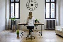Vista posteriore della donna seduta alla scrivania a casa sotto un grande orologio da parete — Foto stock