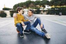 Padre abrazando hijo en la cancha al aire libre de baloncesto - foto de stock