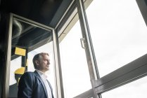 Serious mature businessman looking out of window — Stock Photo