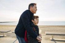 Padre e figlio con scooter sul lungomare al tramonto — Foto stock