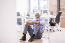 Portrait of african american businessman sitting on the floor of an office — Stock Photo