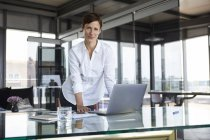 Portrait of confident businesswoman standing at glass table in office with laptop — Stock Photo