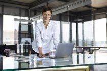 Porträt einer selbstbewussten Geschäftsfrau, die mit Laptop am Glastisch im Büro steht — Stockfoto