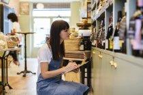 Жінка з дошкою на полиці в магазині. — стокове фото