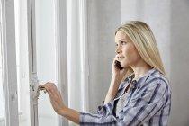 Mujer rubia en el teléfono mirando por la ventana - foto de stock