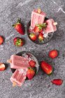 Homemade strawberry ice lollies in bowls — Stock Photo