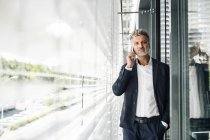 Mature businessman talking on cell phone at outside sunblind — Stock Photo