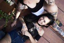 Donna felice sdraiata sulla gamba della fidanzata tatuata su tavole — Foto stock