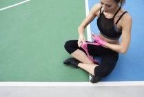 Adatta donna che avvolge le mani per la boxe — Foto stock