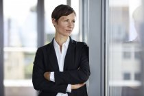 Businesswoman in office looking out of window — Stock Photo