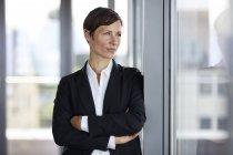 Empresária no escritório olhando pela janela — Fotografia de Stock