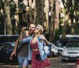 Couple soufflant des bulles de savon dans la ville ensemble — Photo de stock