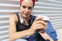 Ritratto di giovane donna con cuffie e caffè da portare — Foto stock