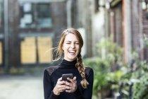 Retrato de mujer risueña con smartphone - foto de stock