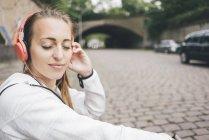 Смолящая спортивная молодая женщина с закрытыми глазами в наушниках на улице — стоковое фото