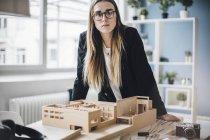 Портрет серьезного архитектора с архитектурной моделью в офисе — стоковое фото
