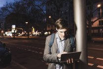 Businessman using laptop on urban street at night — Stock Photo