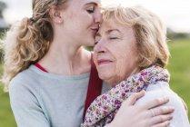 Neta beijando sua avó — Fotografia de Stock