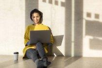 Портрет улыбающейся девушки, сидящей на полу и использующей ноутбук — стоковое фото