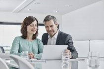 Businessman and businesswoman having a meeting in office with laptop — Stock Photo