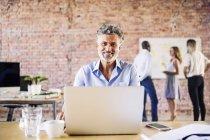 Retrato de un hombre de negocios sonriente en la oficina con colegas en segundo plano - foto de stock