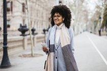 Spagna, Barcellona, donna sorridente con cellulare e auricolari che cammina in città — Foto stock